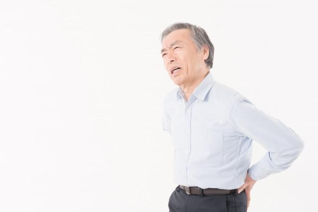 腰を抑えている男性の写真